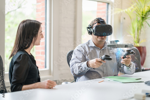 Business colleague wears a virtual reality headset and interacts