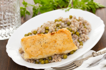 fried fish with boiled buckwheat and peas in white dish