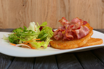 Traditional russian draniki with bacon and salad