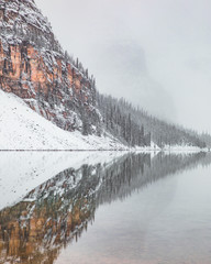 View of mountain reflected in lake during winter