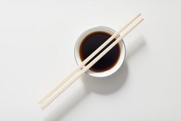 Japanese chopsticks on soy dish. Sushi food.
