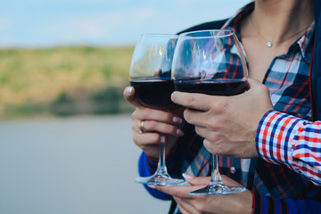 Portrait of a cute couple on date holding red wine glasses