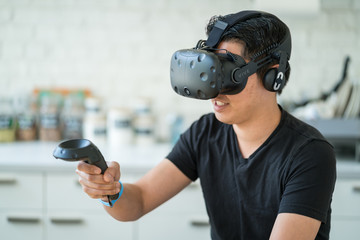 An asian young man uses a virtual reality headset.