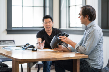 Business colleagues discuss while using a virtual reality headset.