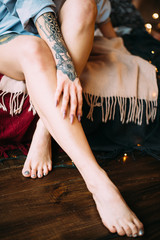 Beautiful woman with dreadlocks and tattoos. Legs and arms closeup. Boho style