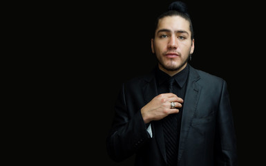 Portrait of a young latin man wearing earring with black suit, black shirt and black tie on black background with his hand on his tie seen from front