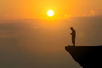 Man praying on cliff against sunset background