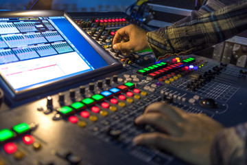 Two hands on a audio mix control board console