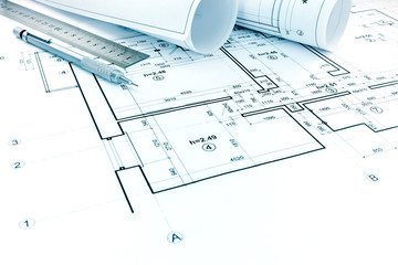 rolls of plans, drawing and measurement tools on architectural project of house