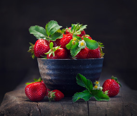 Strawberries in a bowl with leaf and blooming flower close-up over wooden background
