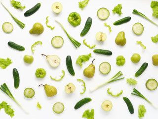 Vegetables and fruits on a white background. Pattern of vegetables and fruits. Food background. Collage of food. Top view.  Composition of cucumber, pepper, lettuce leaves, pear, onion, green radish.