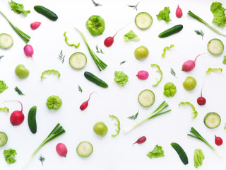 Vegetables and fruits on a white background. Pattern of vegetables and fruits. Abstract food background. Top view.  Food collage of  green radish, pepper, lettuce, cucumber, green apples, onion.