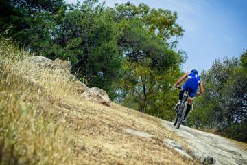 Triathlete mountain bike riding on off road