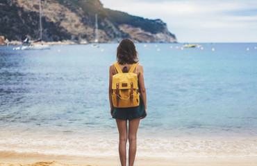 Back view hipster girl with backpack in sand coastline on nature landscape, mock up. Traveler on background beach seascape and horizon mountain. Tourist look on blue sun ocean, summer relax lifestyle