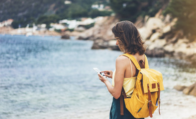 Hipster girl with backpack hold on smart phone gadget in sand coastline, mock up. Traveler using in hand mobile on background beach seascape horizon. Tourist look on blue sun ocean, summer lifestyle