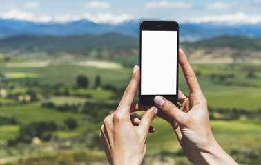 Hipster photograph on smart phone gadget mobile, mock up of blank screen. Traveler hold and using in hand mobile on background mountain landscape horizon. Tourist look map on trip, lifestyle concept
