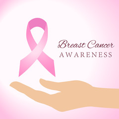 Woman hands holding pink breast cancer awareness ribbon