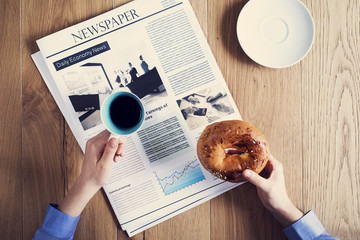 Female hands holding pastry with reading newspaper
