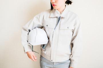 ヘルメットを持つ女性作業員