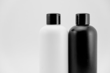 Black and white cosmetic skin care containers and charcoal raw soap package on white isolated background.