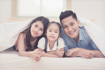 Asian family happy smiling and relax on bed at home. Photo series of family, kids and happy people concept.