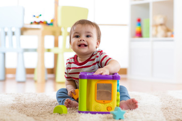 toddler boy playing indoors with sorter toy sitting on soft carpet