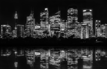Sydney Waterfront at night seen from Farm Cove, with reflections in bay's water