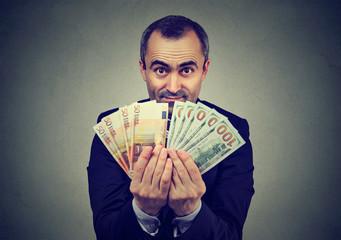 man holding money euro and dollars banknotes