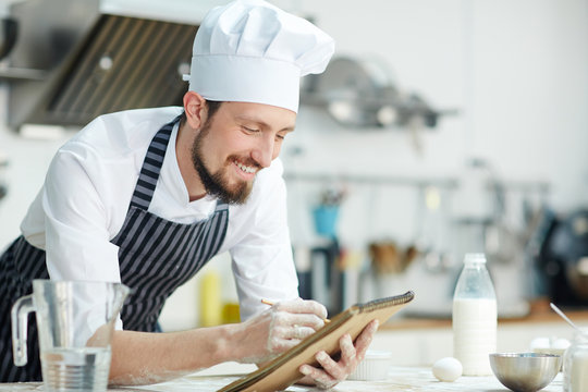 Happy chef writing something in notepad over workplace