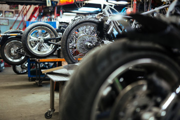 Background image of several motorcycles on stands in repair shop with back wheels in row