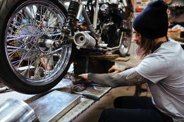 Portrait of tattooed biker working in garage repairing broken motorcycle and customizing it