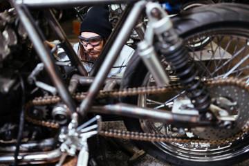Portrait of brutal bearded man assembling custom motorcycle in garage