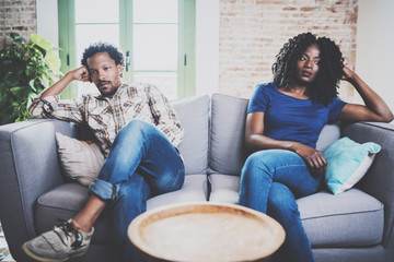Young displeased black couple.American african men arguing with his stylish girlfriend,who is sitting on sofa on couch next to him with legs crossed.Man looking away offended expression on her face. Wall mural