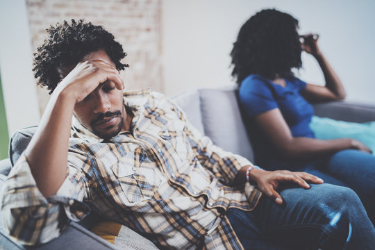 Young sad black couple.Upset man being ignored by partner at home in the living room.American african men arguing with his stylish girlfriend,who is sitting on sofa couch next to him.Blurred