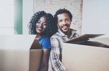 Closeup view of young black african man and his girlfriend moving boxes into new house together and making a successful life.Cheerful family standing in empty new apartment.Blurred background.