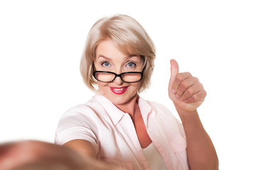 elderly woman with glasses makes selfie and shows thumb over a white background