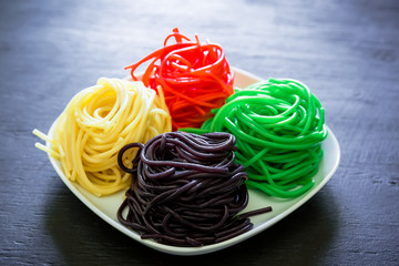 Colorful pasta on white plate on dark table. Tasty vegetarian food