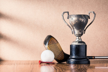 still life photography :  golf club (driver) and ball with old trophy on wood table against  brown wall with window light at left