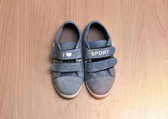 Sports baby sneakers on wood background. love of the sport
