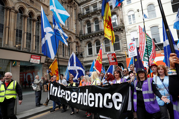 Demonstrators carry flags and hold up a banner at a march in support of Scottish independence in Glasgow