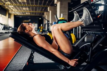 Woman in sportswear trains on exercise machine