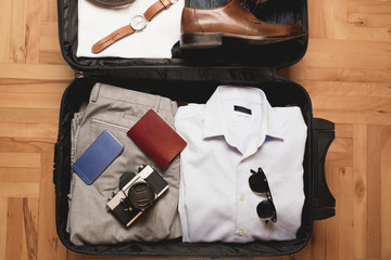 Open traveler's bag with men clothing, accessories, camera, passport, watch and shoes. Travel and vacations concept.