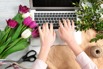 Female florist with laptop and flowers on wooden table