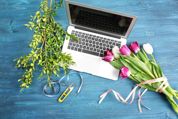 Beautiful flowers and laptop on florist's workplace