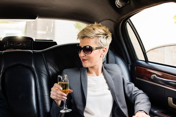 Business woman in limousine having champagne