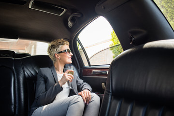 Business woman with glass of champagne in limousine