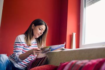 Girl in living room reading magazine