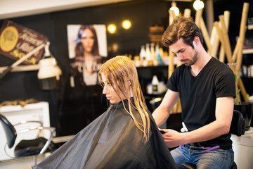 Young male hairdresser with client
