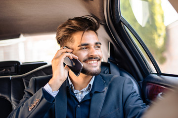 Young man having phone call in limousine