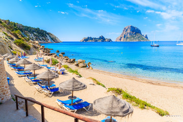 View of Cala d'Hort beach with sunbeds and umbrellas and beautiful azure blue sea water, Ibiza island, Spain Wall mural